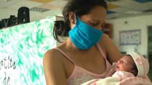 A new mother holds her baby, sleepy and full of breast milk, at a UNICEF-supported breastfeeding workshop at a health center in Caracas, Venezuela.