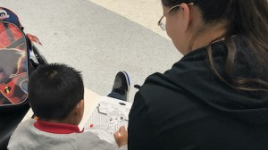 A 5-year-old boy who was separated from his parent after the two arrived at the U.S. border and spent a year away from family in U.S. custody waits to board plane to his home country, with his child advocate from the Young Center by his side.