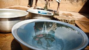 Children fill containers with water from a communal foot-activated pump, in the village of Kiendi-Walogo, Zanzan Region. A reflection of two children is in the closest water bowl.