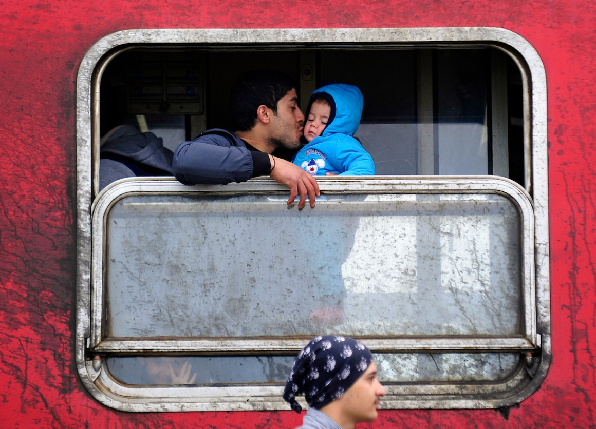 A father kisses his baby boy inside a train filled with refugees from Syria and Iraq travelling across Macedonia to the Serbian border, where they will continue their journey.