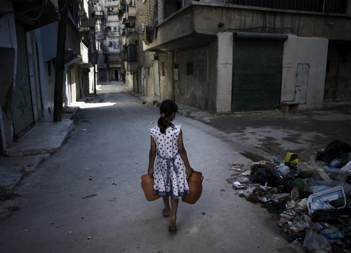 A girl, carrying jerrycans of water, walks past a pile of debris, on a street in Aleppo, capital of the north-western Aleppo Governorate. The city, which has been a site of prolonged fighting during the conflict, is experiencing frequent interruptions in