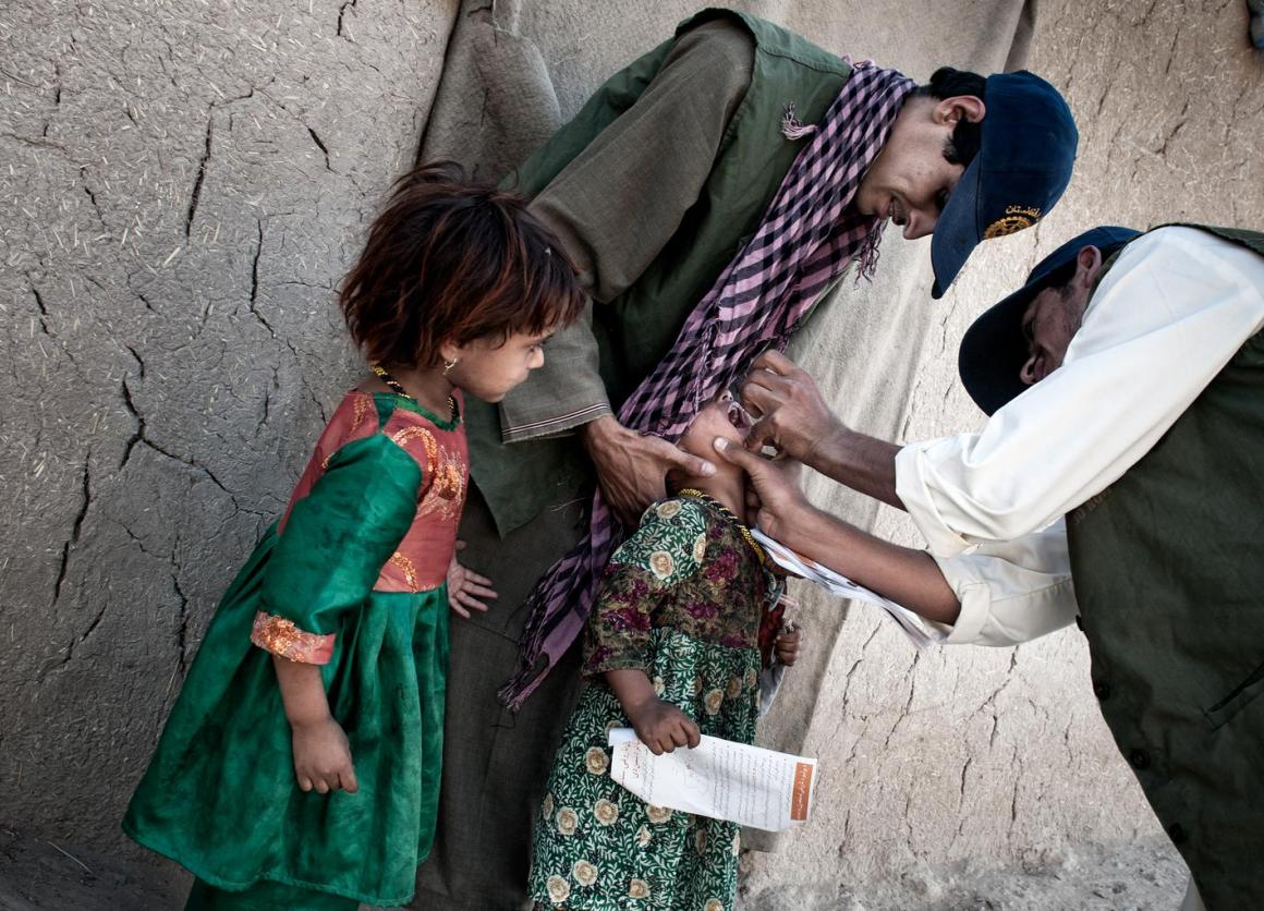 A vaccination worker administers a dose of oral polio vaccine to a girl Kandahar (July 2013).