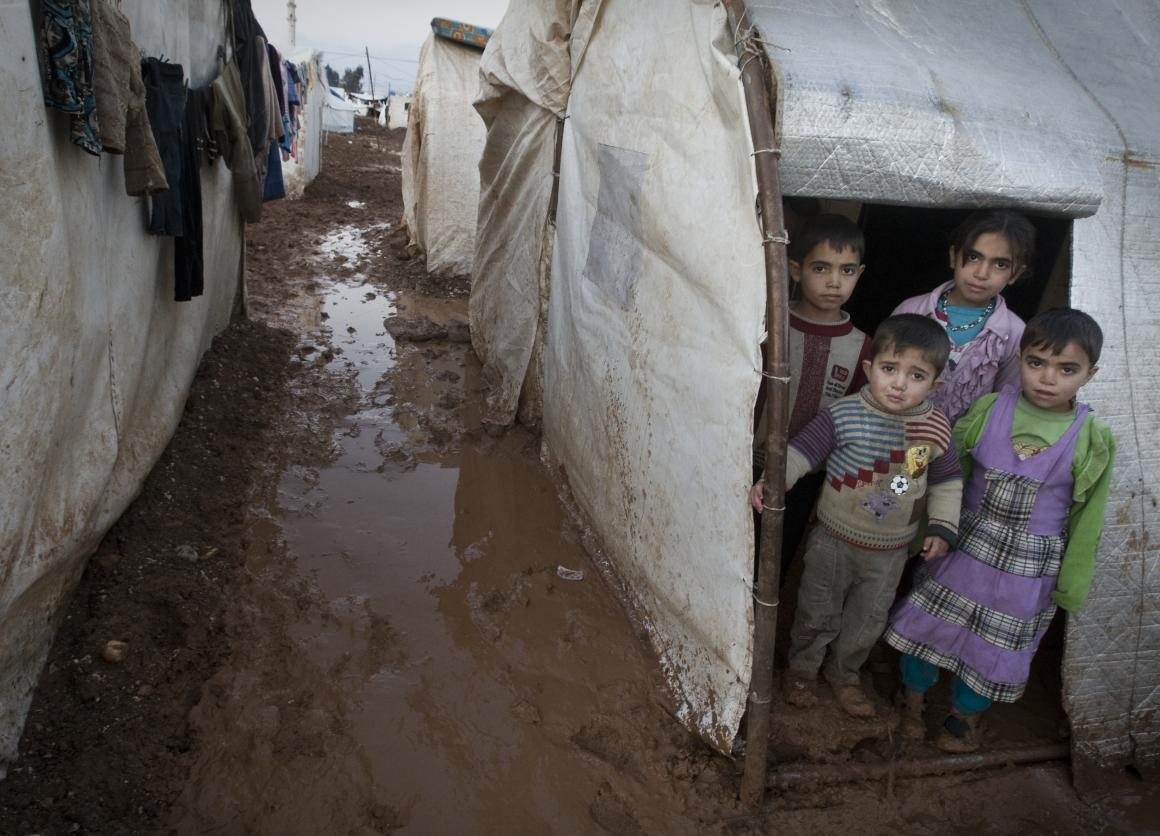 On 1 January, children stand in the entryway of their tent shelter, in the Bab Al Salame camp for internally displaced persons, near the border with Turkey, in Aleppo Governorate. © UNICEF/NYHQ2014-0003/Diffidenti;