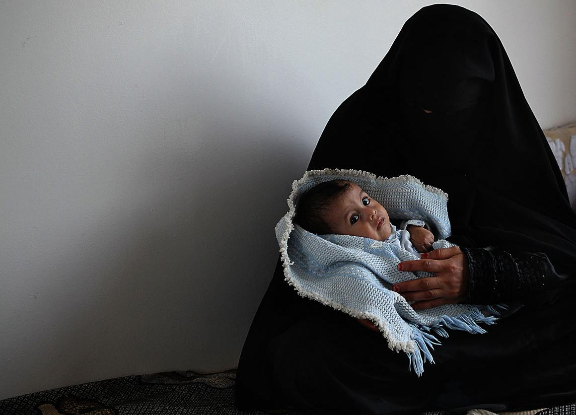 A five-month-old  is cradled by his mother, at the UNICEF-supported therapeutic feeding centre