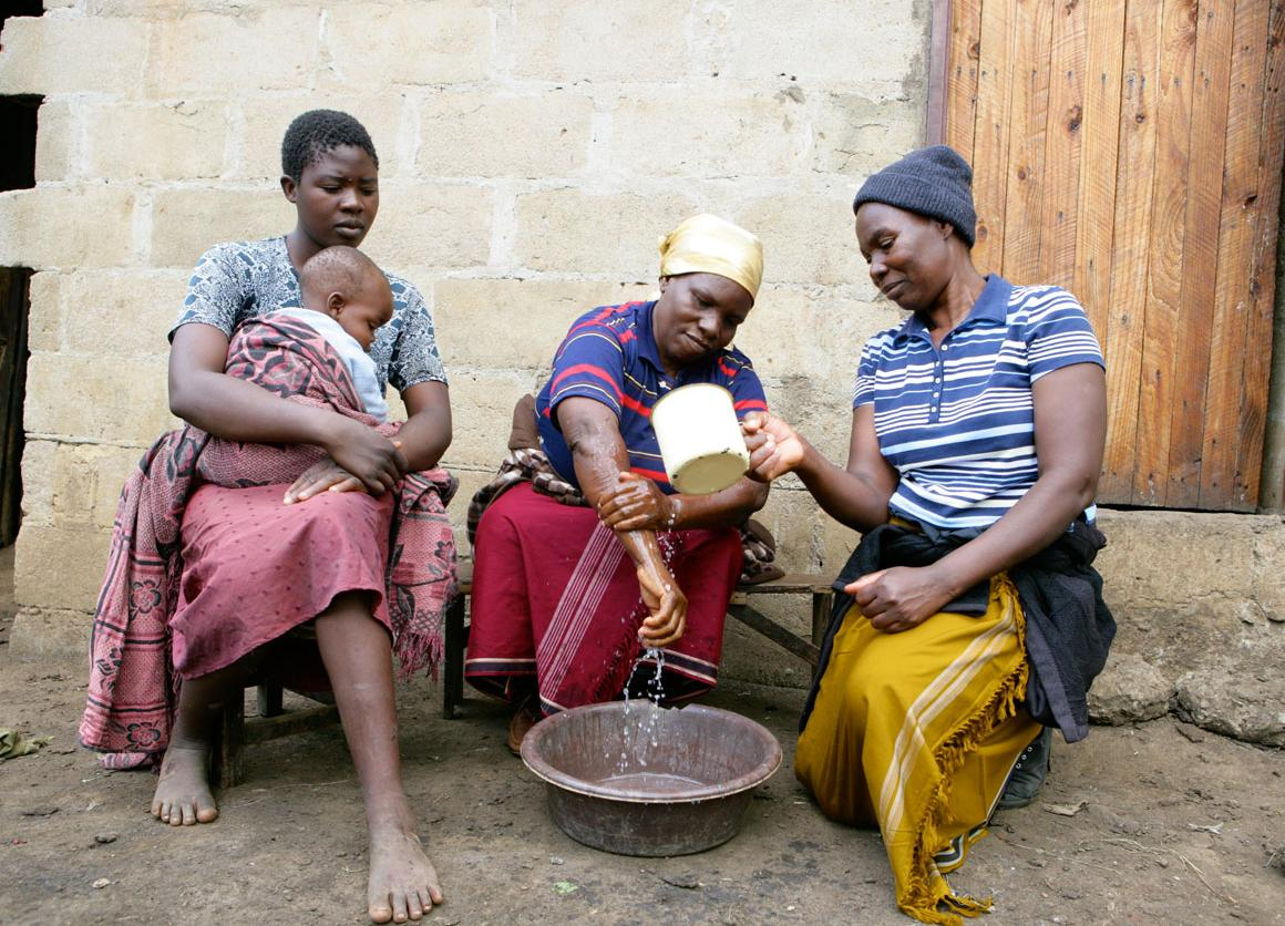 2011, Two community health workers in Hatcliffe Extension, Harare demonstrate to Linda Tigere how to wash hands properly using soap to prevent disease. Linda and her son survived a cholera outbreak that claimed her mother's life in 2008.