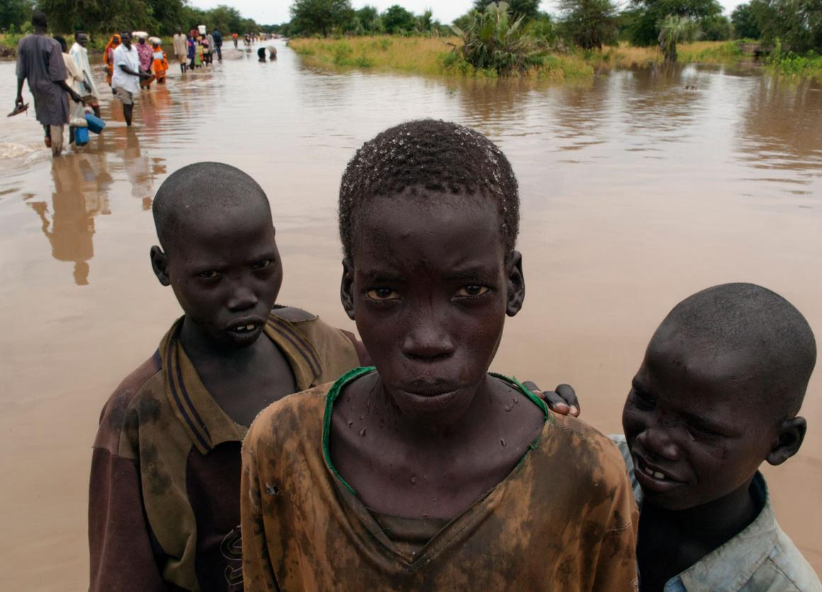 Boys stand in waters caused by seasonal flooding, on a road in South Sudan. Behind them, other pedestrians wade through the water. The county is home to four camps for Sudanese refugees.