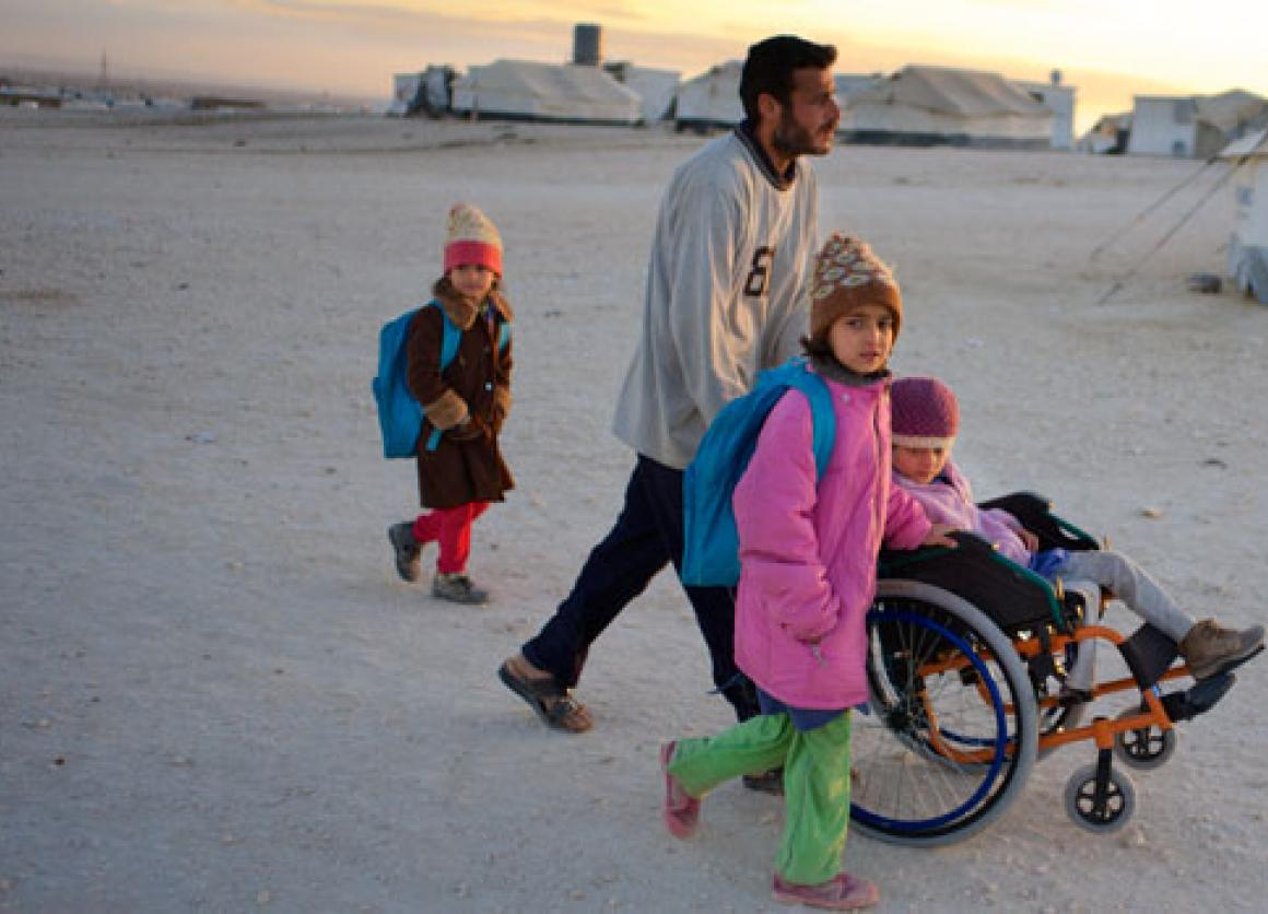 On 26 November 2013 in Jordan, Ahmed pushes his daughter Safa, 6, in a wheelchair through a refugee camp.