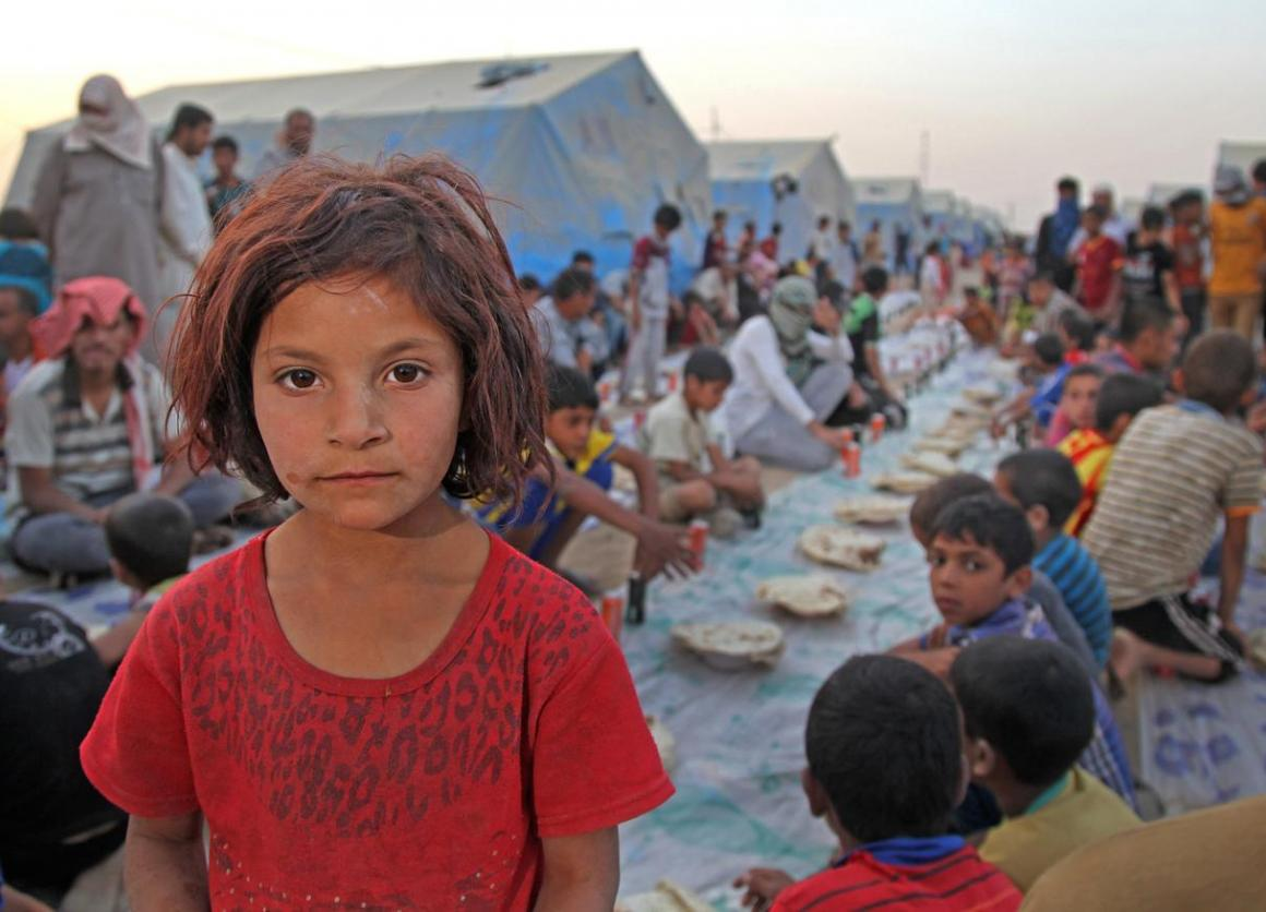 A girl is among displaced children and adults who have gathered for 'Iftar' in the Khazar transit camp in the northern-eastern city of Erbil, capital of Kurdistan Region.