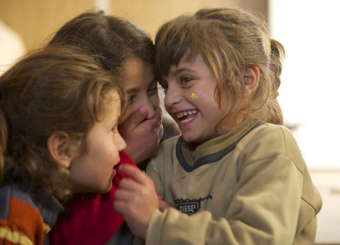 Safa (right), 6, laughs with her twin sister, Marwa (left), and 9-year-old sister, Aya (centre), in their family's caravan, in the Za'atari refugee camp,