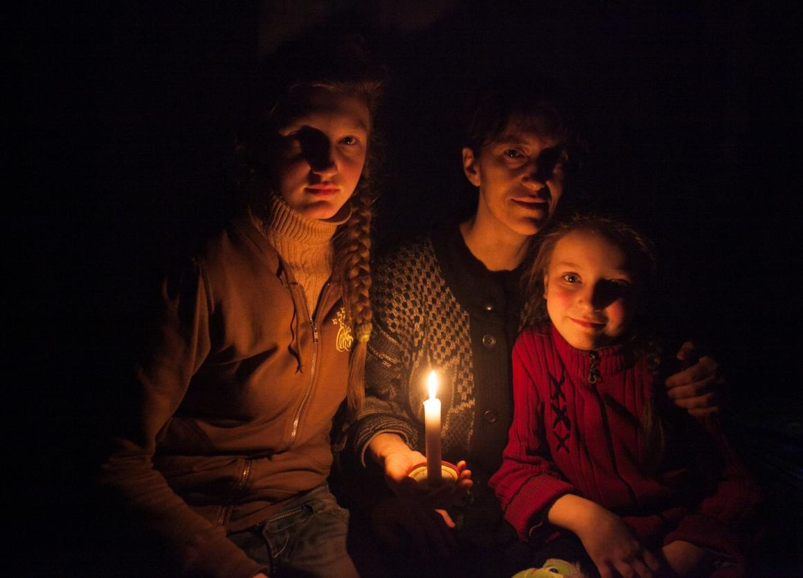 A woman and her daughters sit in candlelight in a bomb shelter on the outskirts of the city of Debaltsevo, Ukraine – where fighting has continued despite the ceasefire agreement.