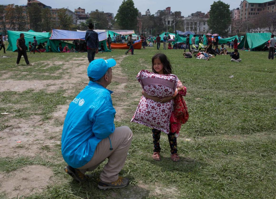 A UNICEF worker speaks to a child seeking temporary shelter in Kathmandu following Nepal's massive earthquake. © UNICEF/NYHQ2015-1007/Nybo