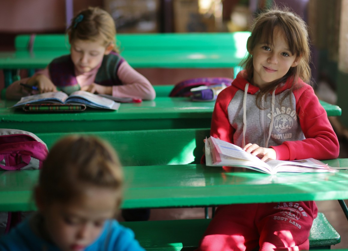 A girl reads during a class in School No. 6 in Yasinovataya, Donetsk region, Ukraine, 24 October 2016.