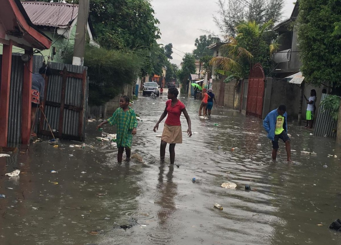 On 7 September 2017 in Haiti, children and women wade through a street in Hinche as Hurricane Irma approaches.
