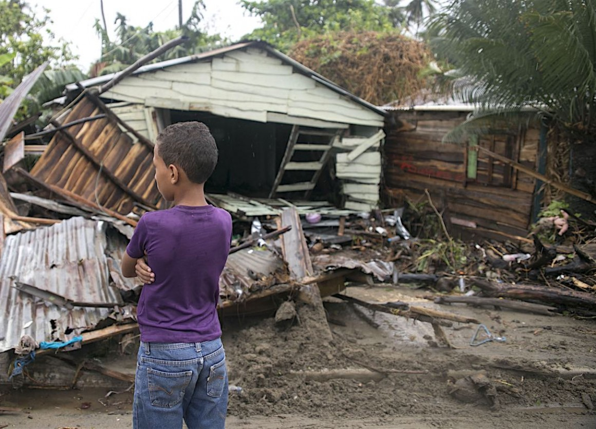 On September 7, 2017 in Boba, Nagua, a boy, 7, stands in front of debris as Hurricane Irma moves off from the northern coast of the Dominican Republic.