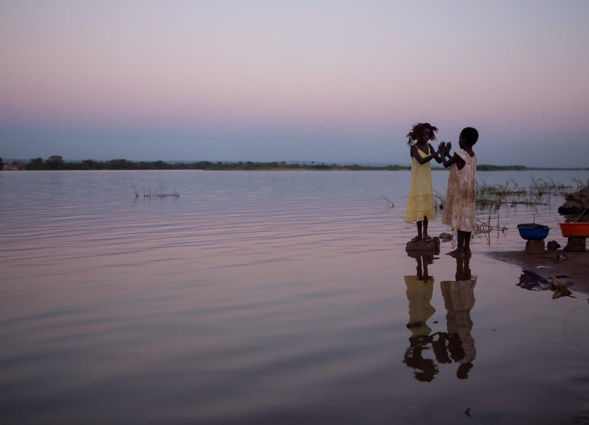 Two young girls play happily on the banks of the Luapala river at sunset in the Democratic Republic of the Congo.