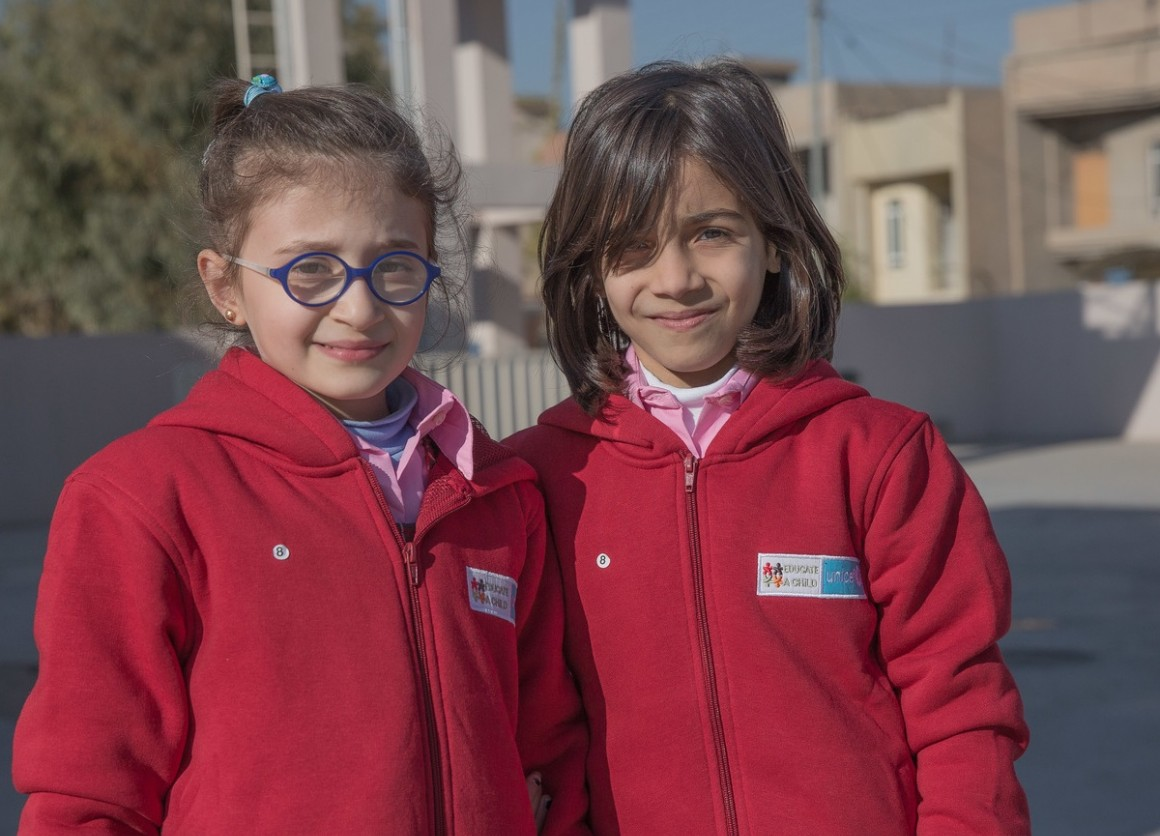 Arah (right) and Saba (left), Syrian refugees living in the Kurdistan Region of Iraq, wear their new winter uniforms at Rubar School in Erbil.