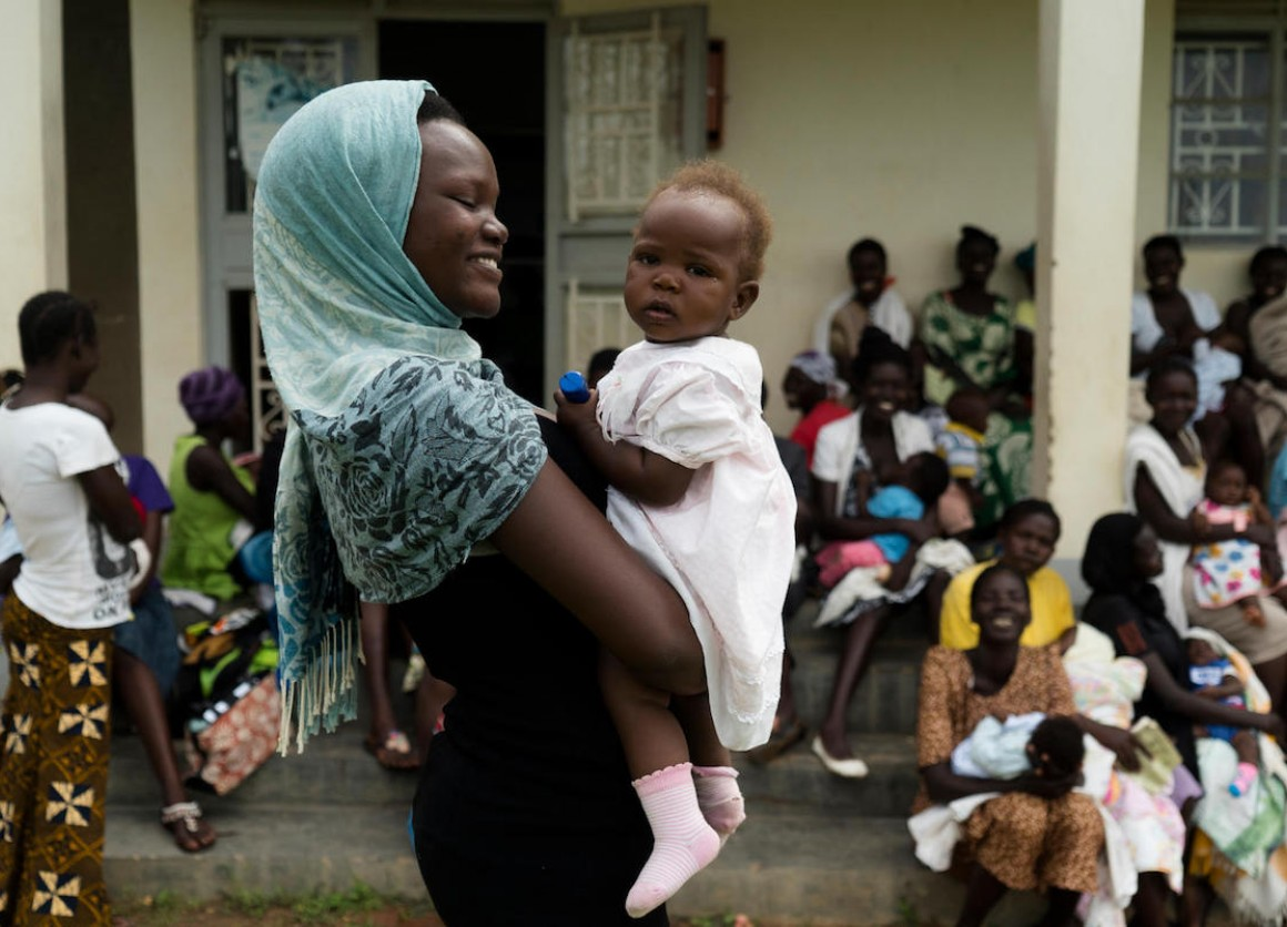 Anirworth Winnie, 17, holds her 7-month-old daughter, Delight, outside the UNICEF-supported Health Center in Nyaruvur, West Nile, Uganda.