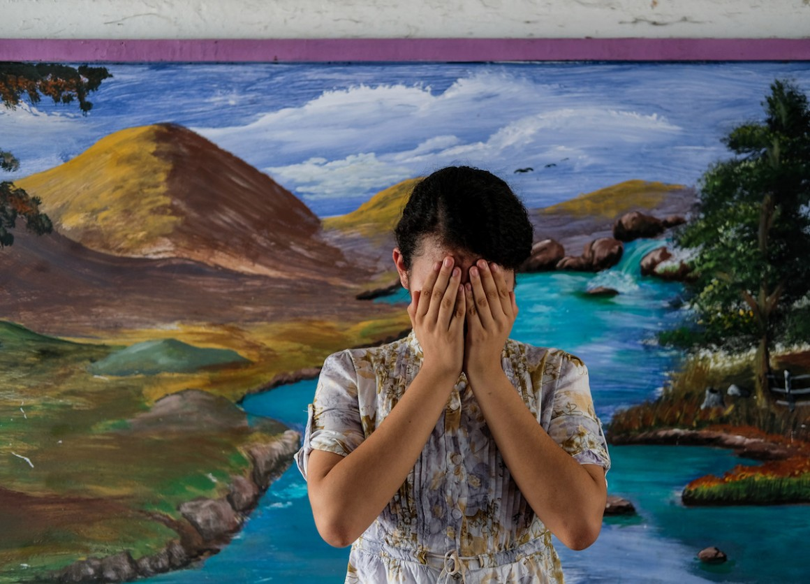 Patricia, 14, covers her face at a school in San Salvador, El Salvador.