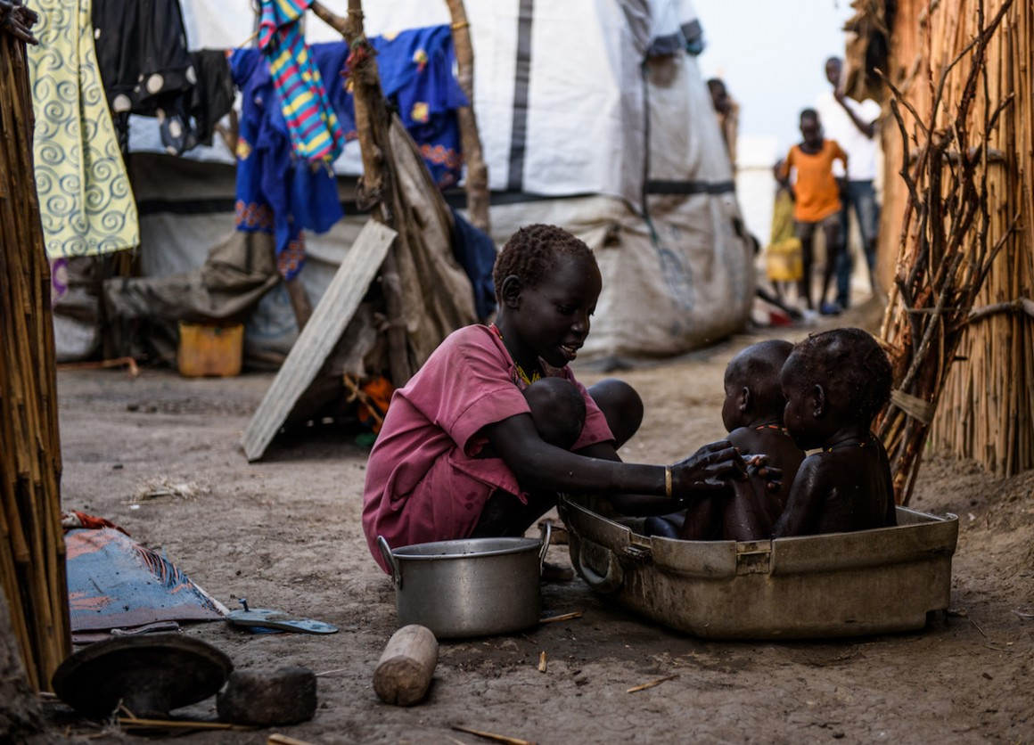 A young girl washes her siblings in the shell of a damaged suitcase in the Protection of Civilians (PoC) site in Bentiu, South Sudan, May 2017.