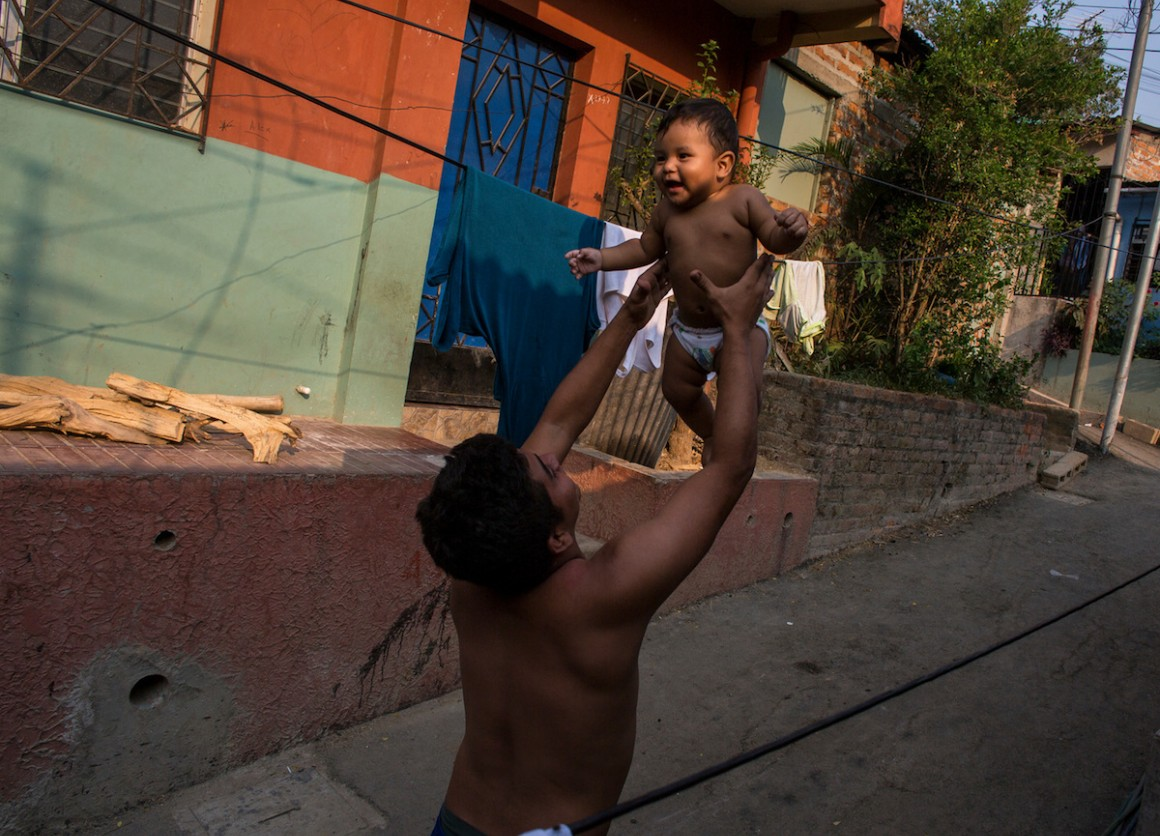 A father holds his infant son in San Salvador, El Salvador.