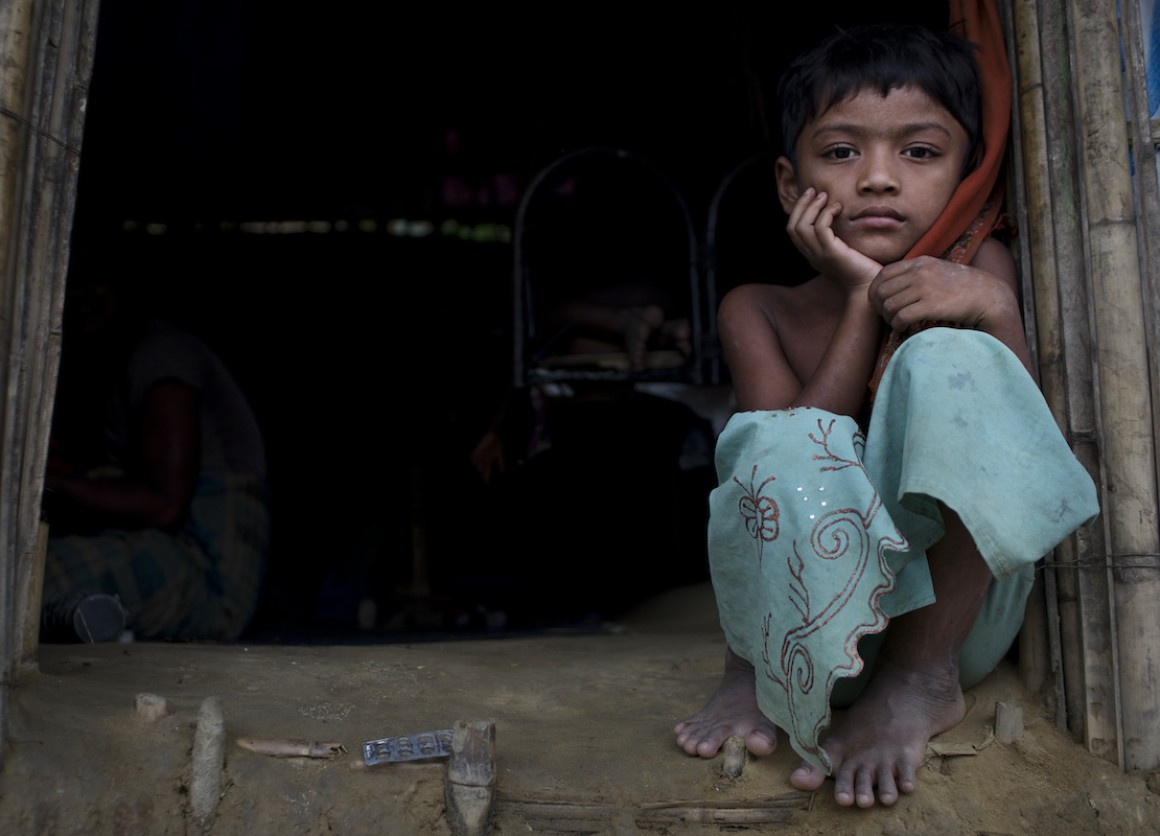 Murium Begu, 7, sits by the entrance of her home in Chakmakul, a refugee camp sheltering over 800,000 Rohingya refugees, in Cox's Bazar, Bangladesh.