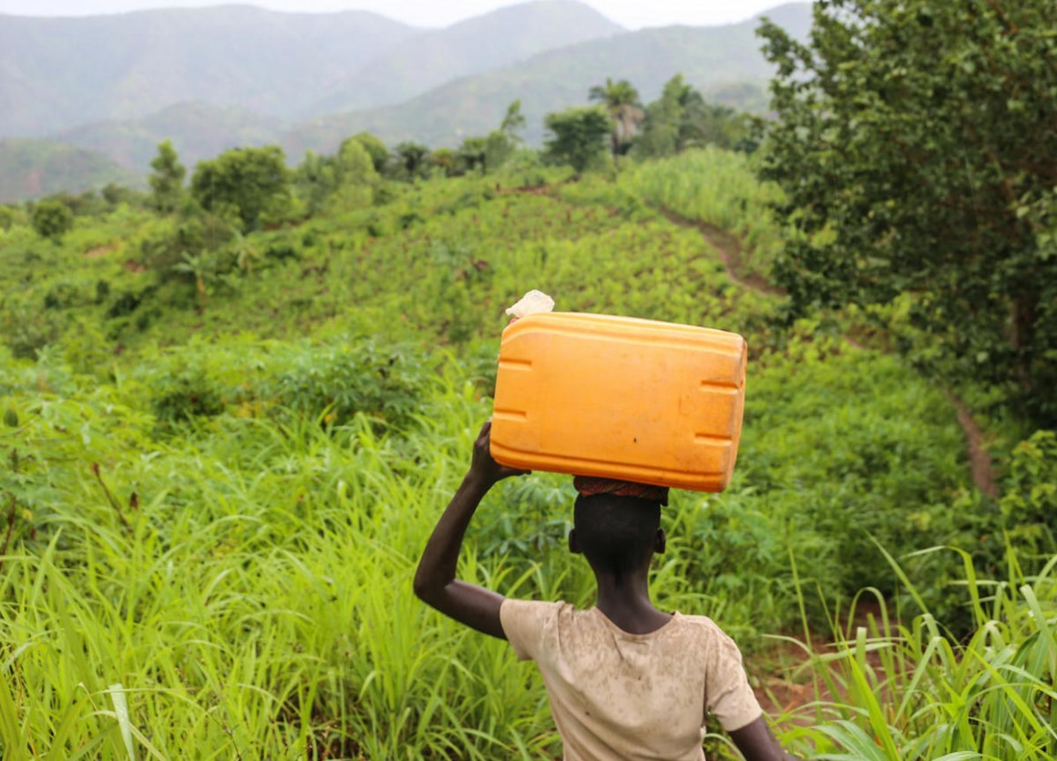 Liliane, 14, carries an empty container as she makes her way to collect safe drinking water in Mukerezi-Mpakaniro hill, Makamba Province, Burundi, January 2017.