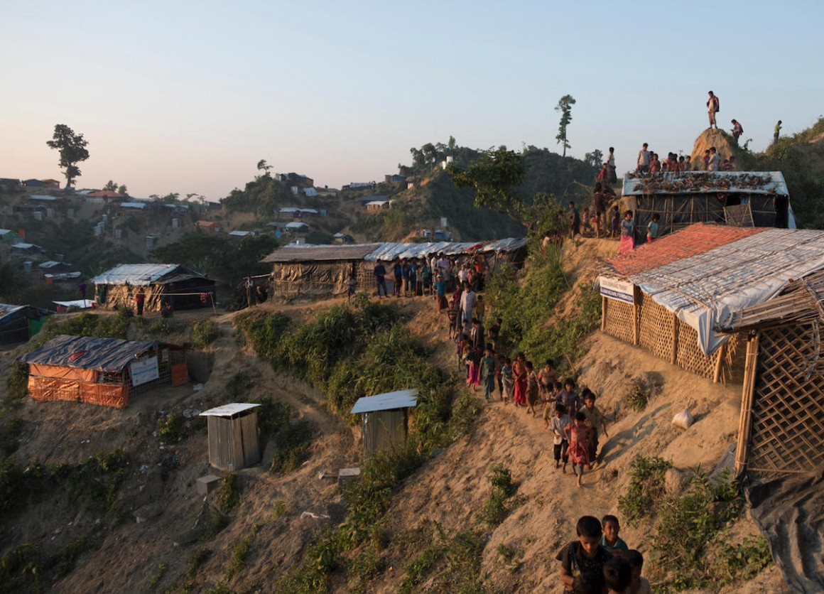 Rohingya refugee children walk along a narrow path hugging a steep slope at the Unchiprang spontaneous site, Cox's Bazar District, Bangladesh, January 2018.