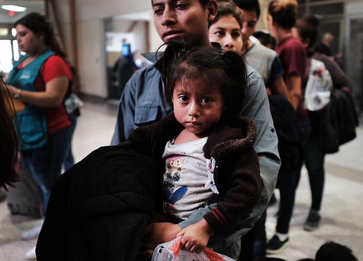 A Guatemalan father and his daughter arrive with dozens of other women, men and children at at bus station following release from Customs and Border Protection in McAllen, Texas.
