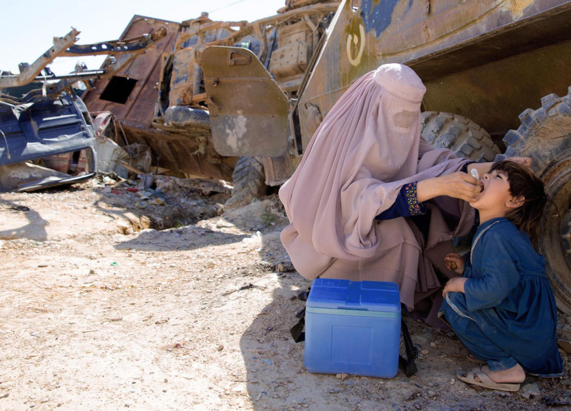 UNICEF-supported polio worker Afia (name changed), 19, vaccinates a child in an old military barrack in Afghanistan in March 2018.