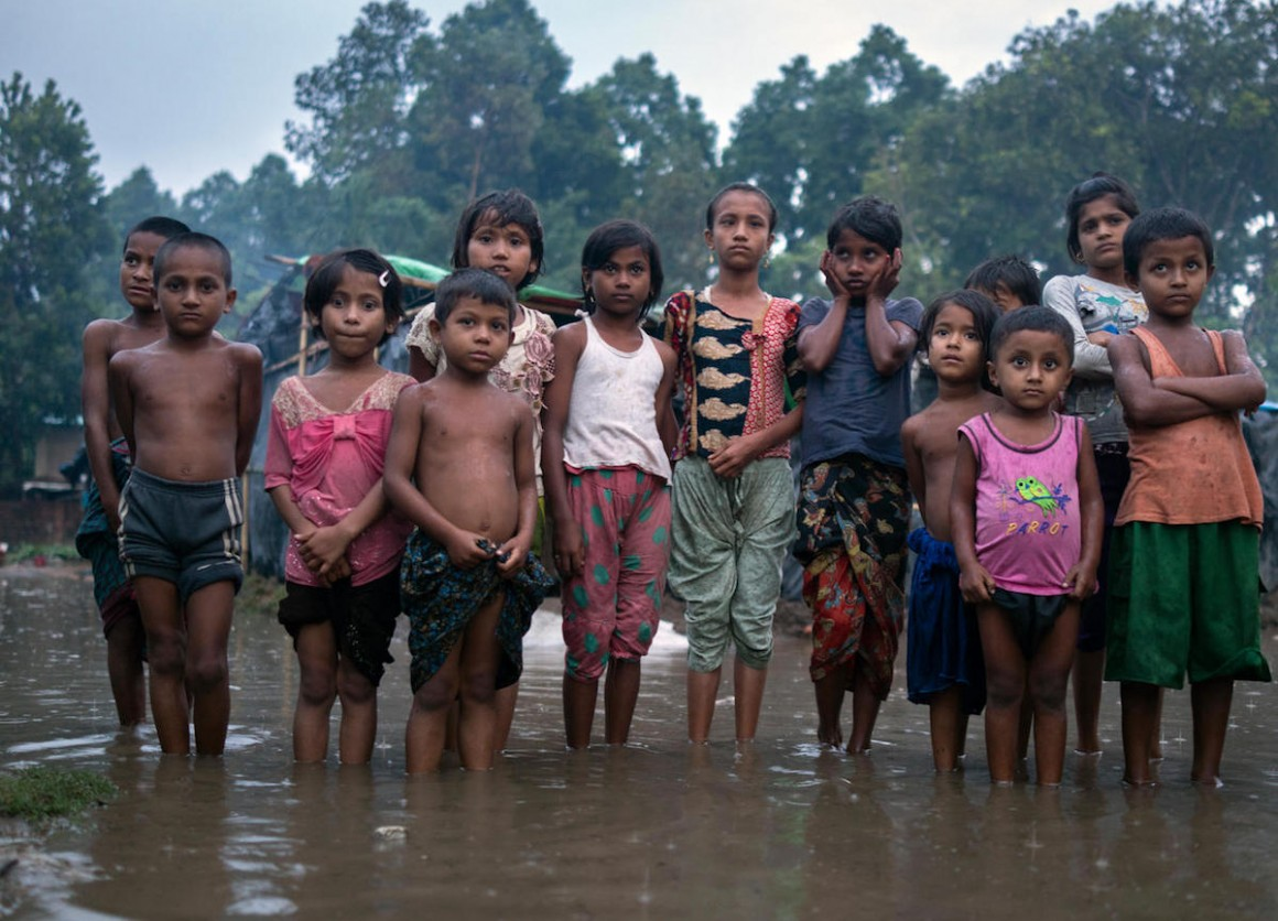 Rohingya refugee children wade through flood waters in Shamlapur Makeshift Settlement, Cox's Bazar district, Bangladesh on May 20, 2018.