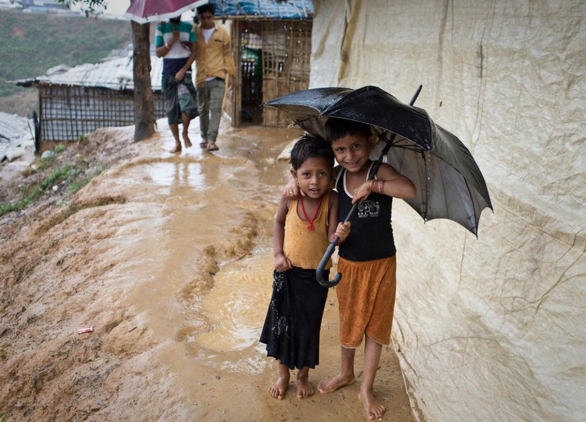 children smile as they shelter from the rain in Balukhali-Kutupalong, a refugee camp sheltering over 800,000 Rohingya refugees in Cox's Bazar, Bangladesh.
