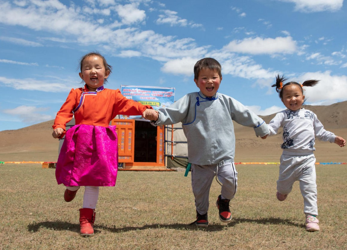 In June 2018 in Mongolia, three preschool-age children run hand-in-hand outside their mobile 'ger' kindergarten in the Janjin bagh area in Bayankhongor Province.