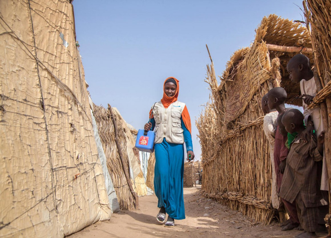 Aisha, a UNICEF-supported polio team vaccinator, walks through Muna Garage IDP camp in Maiduguri, Borno State, northeast Nigeria in January 2018.