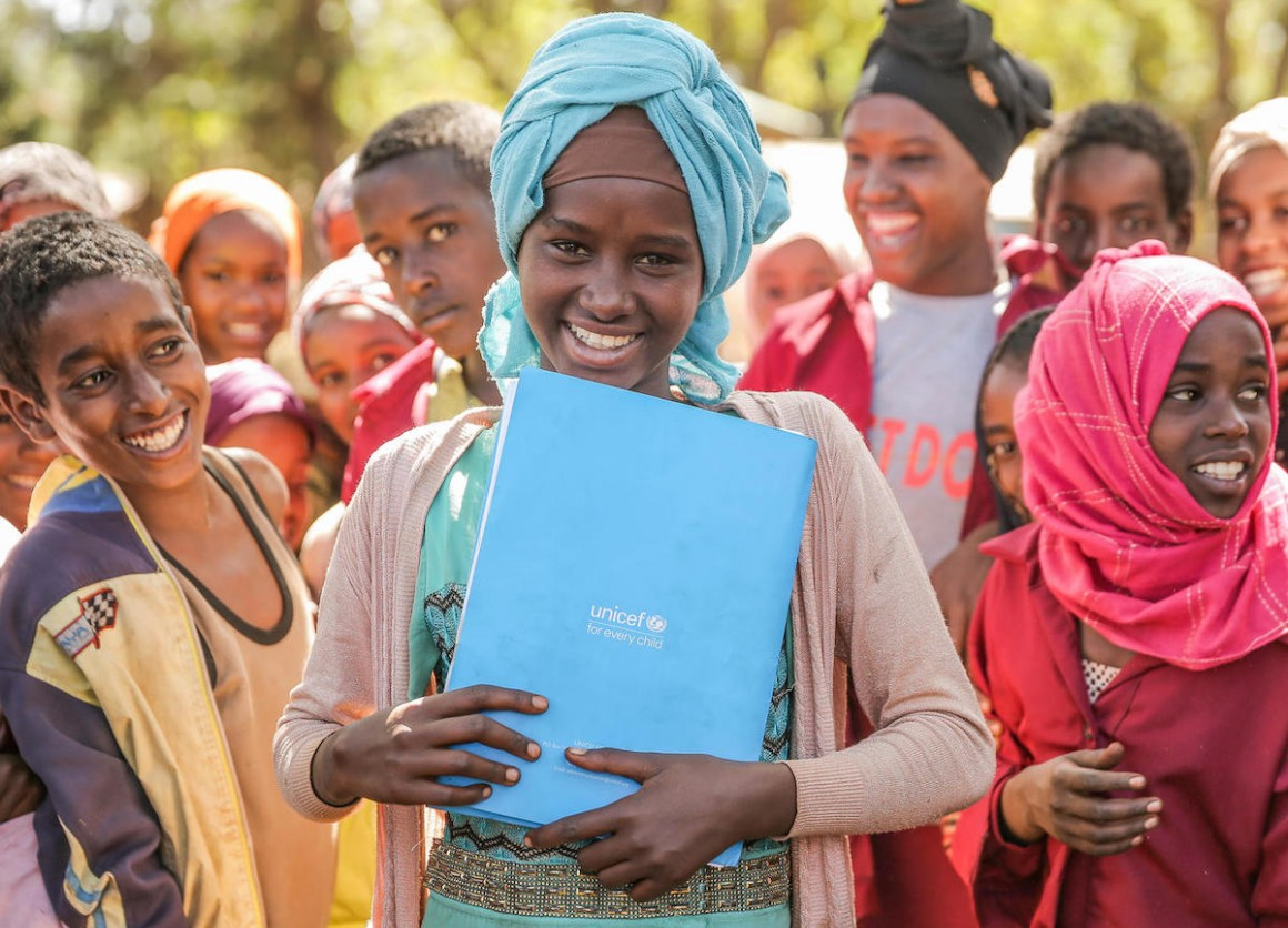 Surrounded by her classmates, a girl holds her UNICEF notebook at Shawe Primary School, Harana Buluk Woreda, in Ethiopia's Oromia Region in 2019.
