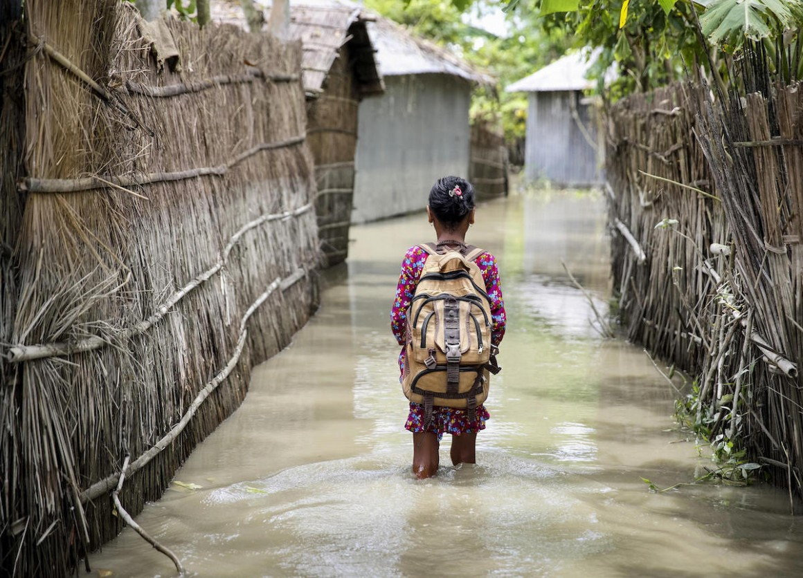 A child wades through flood water on her way to school in the Kurigram district of northern Bangladesh during monsoon season, August 2016.