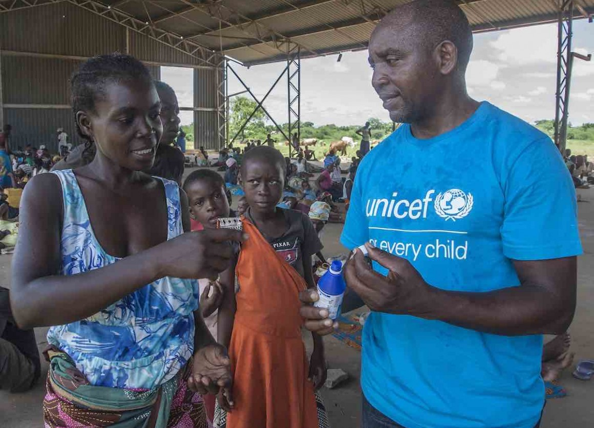 On 21 March 2019 in Malawi, UNICEF WASH Officer Alan Kumwenda shows Anne Joseph, 24, how to use water guard. Anne lost her home in the floods. She saved her children, including 1-week-old Ndaziona, with just minutes to spare. The house collapsed behind th