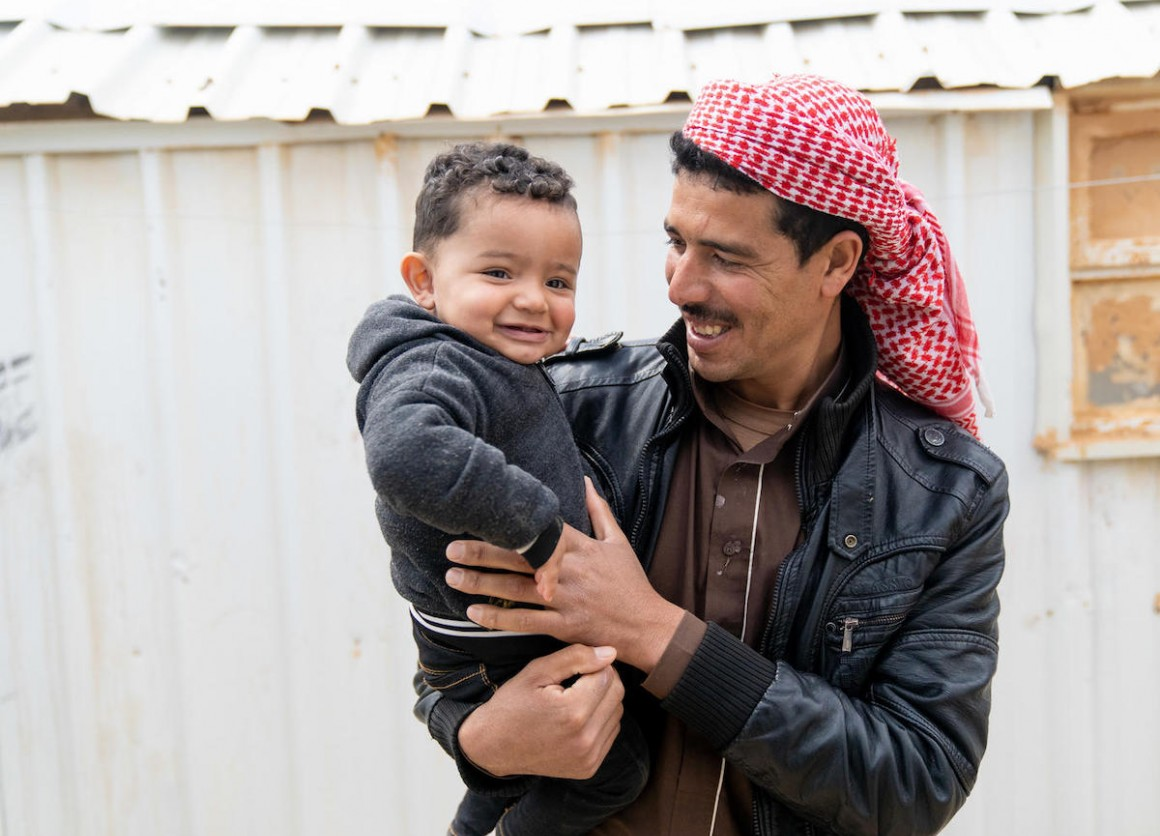 Syrian refugee Shaheen holds his 1-year-old son, Mohammad, in Jordan's Azraq refugee camp. Mohammad was born in the camp's UNICEF-supported pediatric ward.