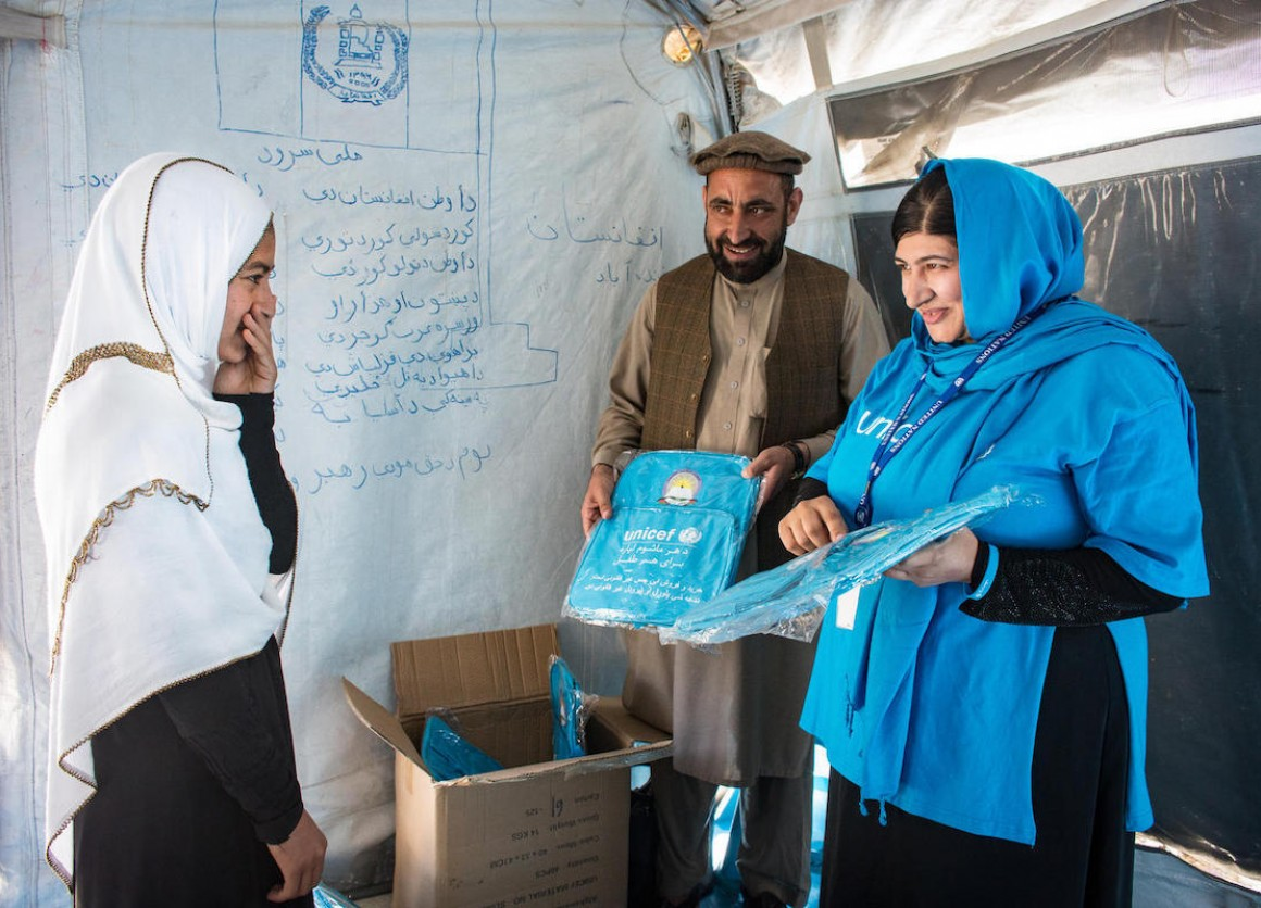 UNICEF Education Specialist Anita Haidary and colleague hand out school bags to an excited student at a UNICEF-supported school in Nangarhar, Afghanistan in 2019.