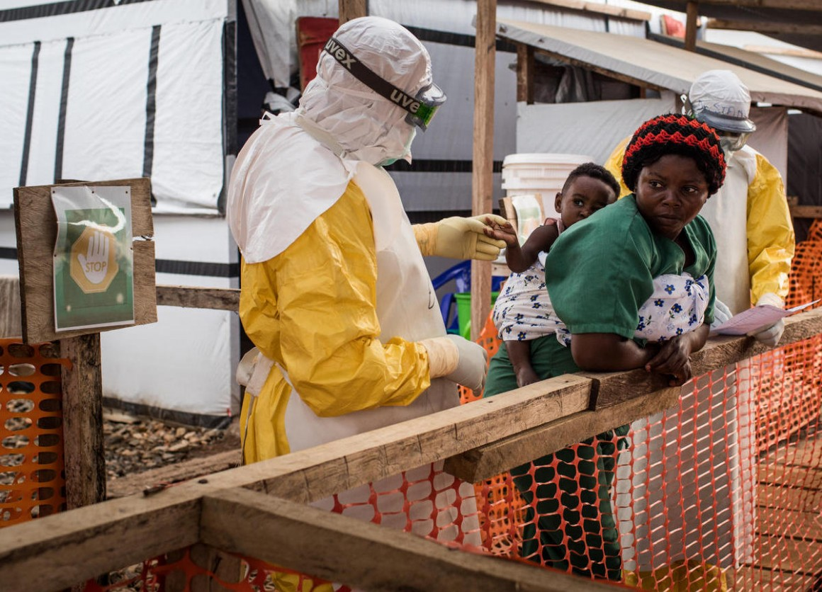 A health worker wearing a gown, gloves and goggles checks a child potentially infected with Ebola being carried on the back of a caregiver at the Ebola Treatment Center of Beni, North Kivu province, Democratic Republic of Congo on March 24, 2019.