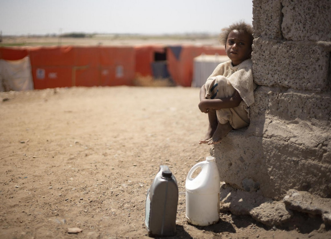 A child from Yemen's Al-Meshqafah camp takes a break while carrying heavy jugs of drinking water from the supply tanks to the camp in February 2019.