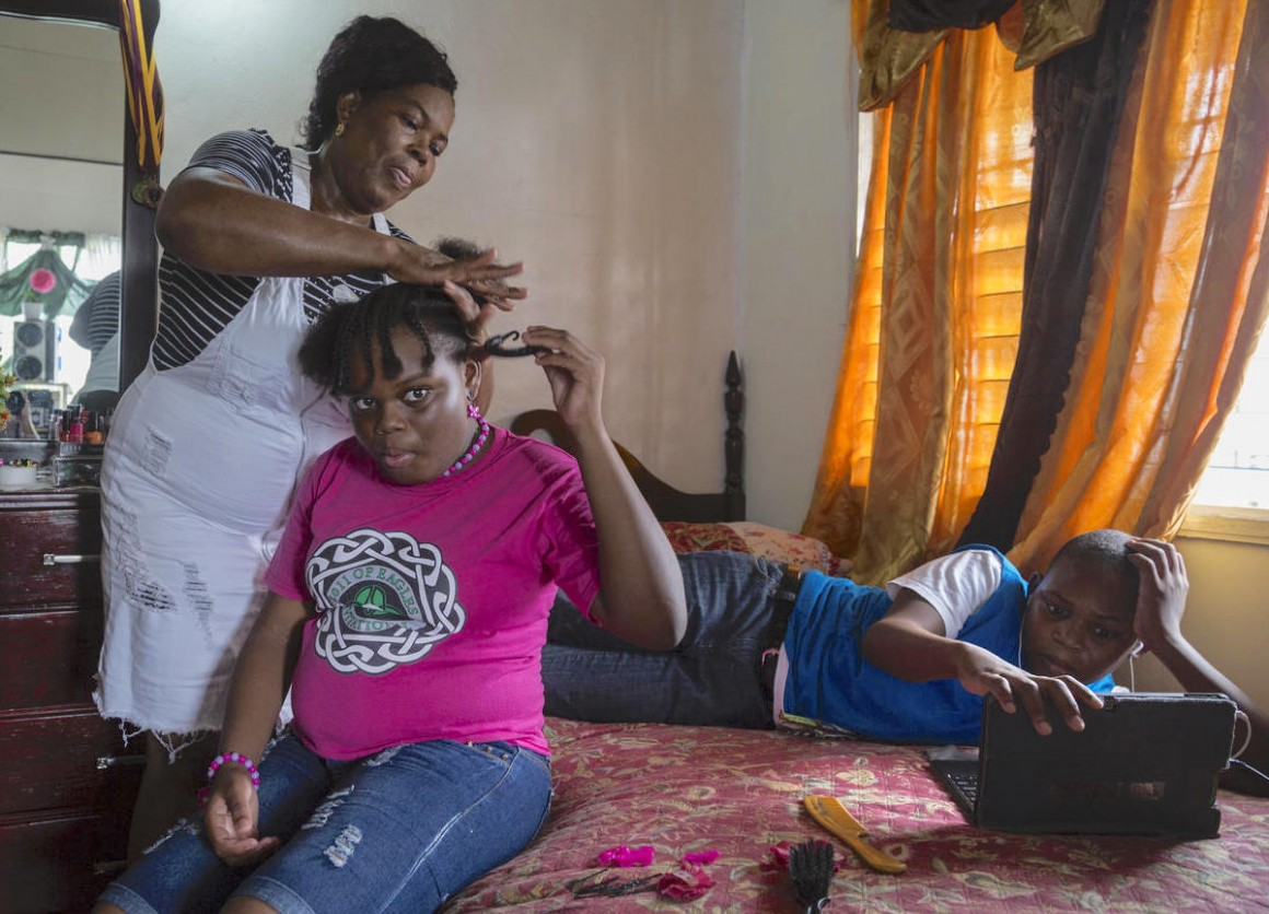 Corine Gerald and her children Jerrene, 11, and James Jr., 13, in their rental house in Antigua. The family was displaced from their home in Barbuda by Hurricane Irma in 2017.