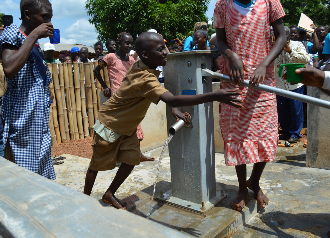 Children in Guinea gather water from a UNICEF-installed water pump in N'Zerekore