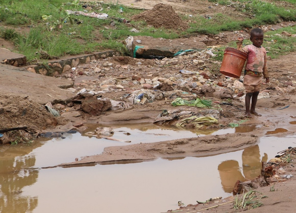 A child plays in a muddy road in the Kinama neighborhood of Bujumbura, Burundi after torrential rains flooded the region.