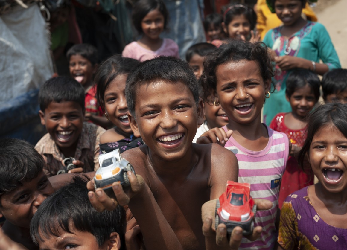 Mohammad Rifat, 12, (shirtless, center) and his friends race toy cars down a sandy stretch of trail in Shamlapur camp, Cox's Bazar District, Bangladesh on April 22 2018