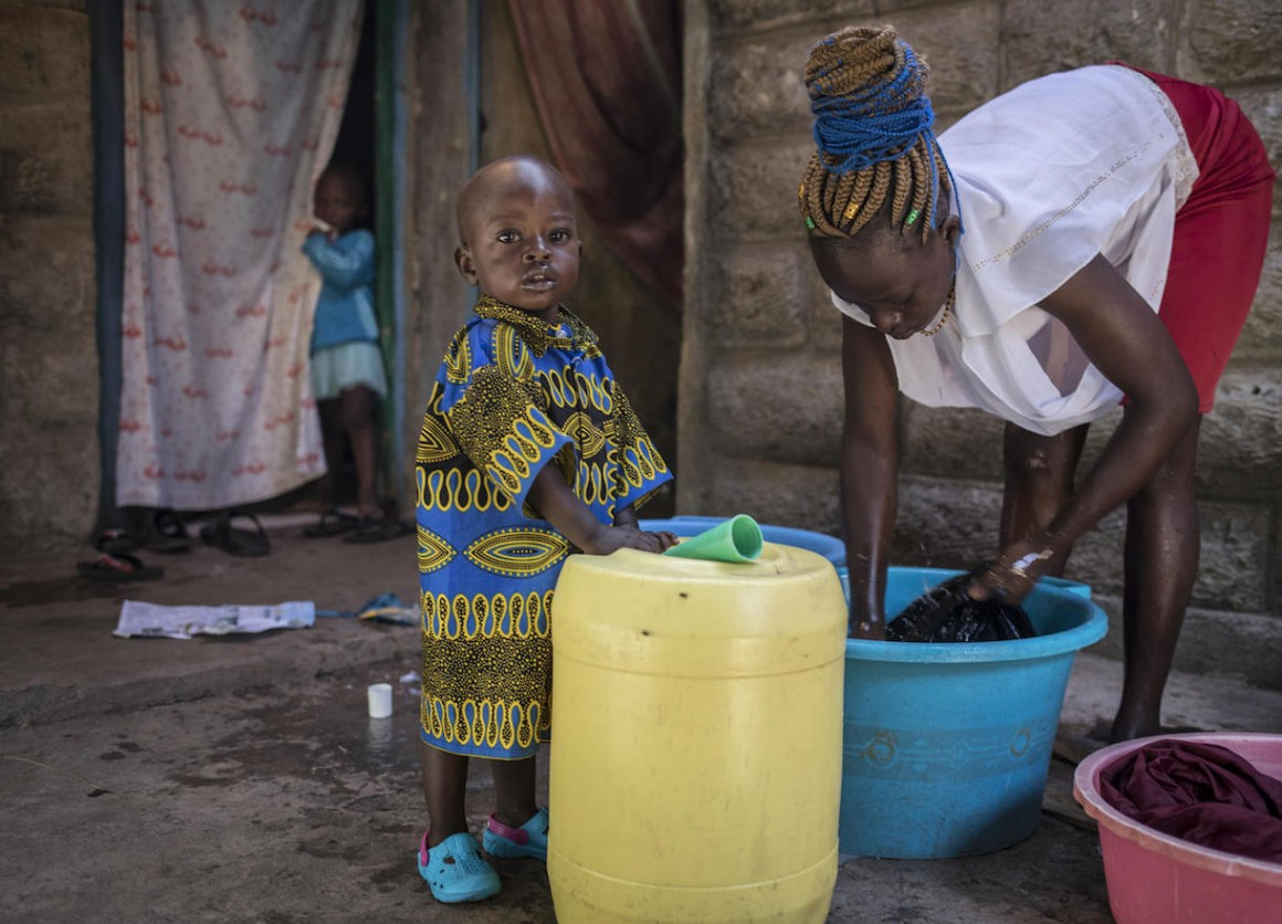 On 3 October 2020 in Kenya, Cinderella Akinyi Othiambo, 22, washes clothes as her one-and-a-half-year-old nephew, Duncan Makoa, looks to the camera, outside her home in Mathare, an informal settlement in Nairobi.