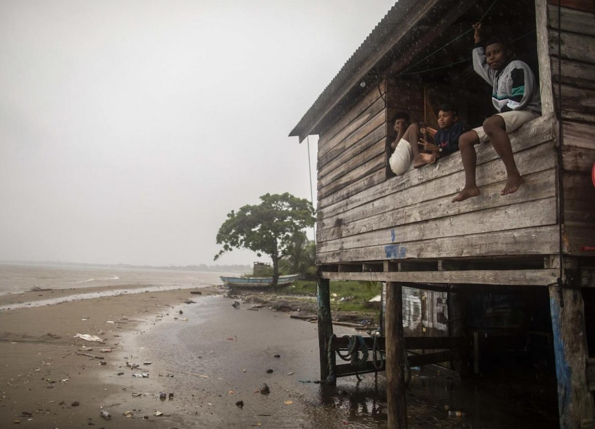 Children sit on a beach house window ledge as Hurricane Eta approaches in Bilwi, Puerto Cabezas, Nicaragua, on November 2, 2020.