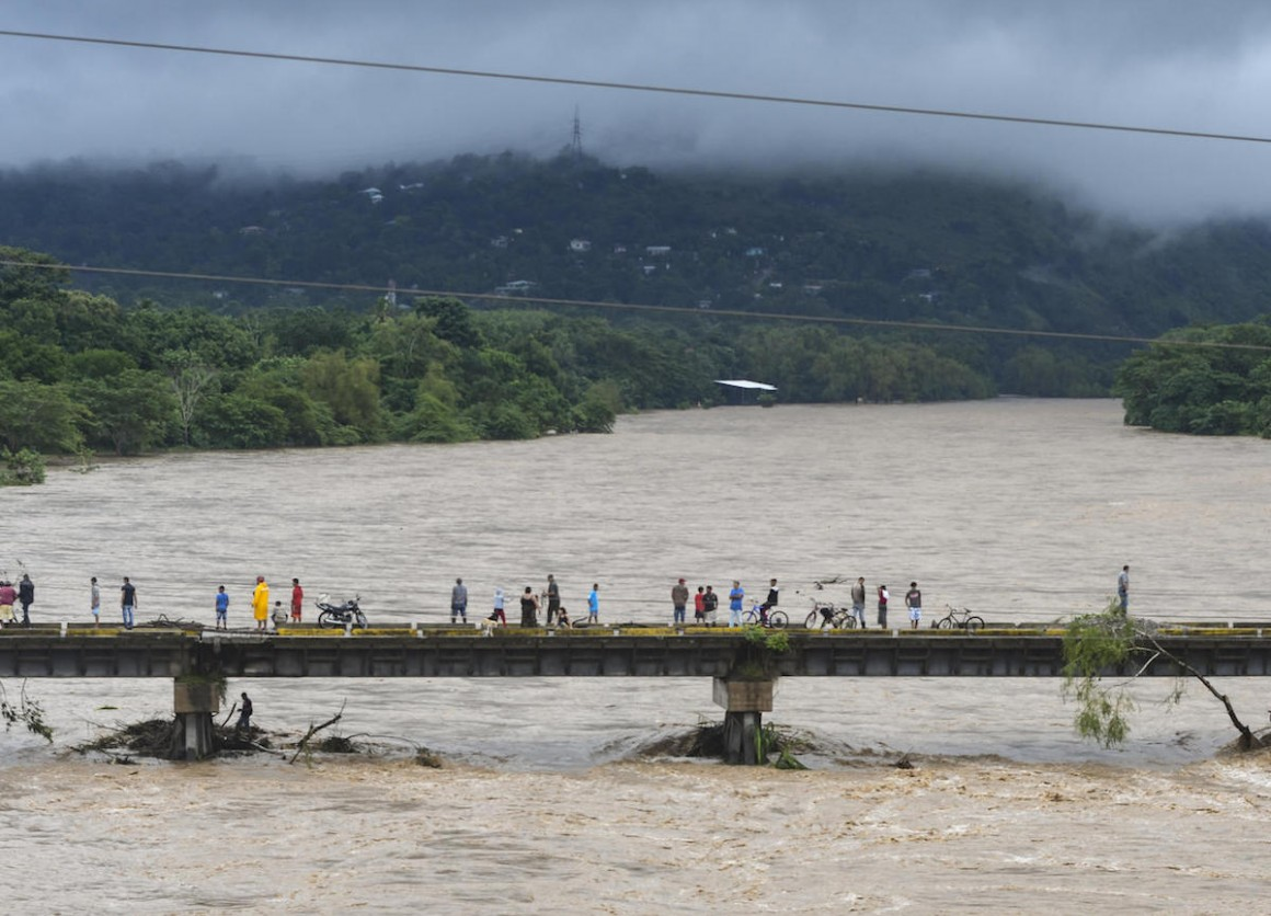 People watch the Humuya river flooding due to heavy rains caused by Eta Hurricane, in Santa Rita, Yoro department, 240 km northern Tegucigalpa, on November 3, 2020.