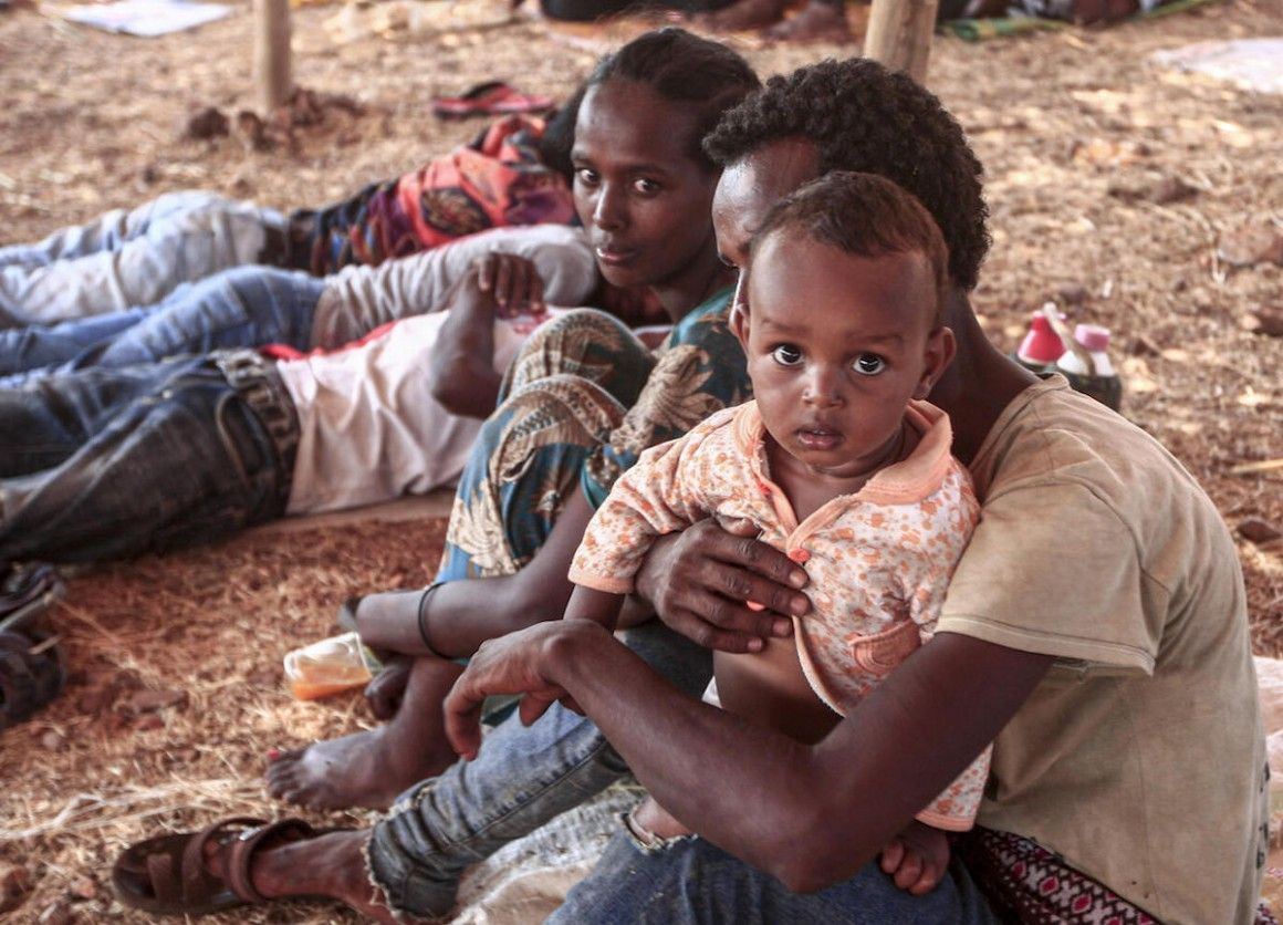 An Ethiopian refugee who fled fighting in Tigray province sits holding a child in a hut at the Um Raquba camp in Sudan's eastern Gedaref province, on 16 November 2020.