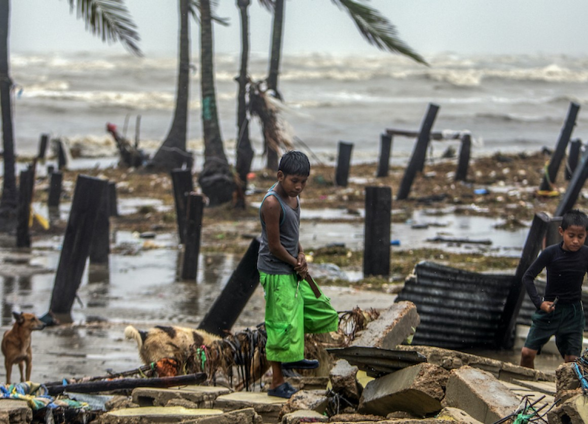 Two boys in Bilwi, Nicaragua, search for scraps of wood to help their parents rebuild their house after it was destroyed by the strong winds and rains brought by Hurricane Iota.