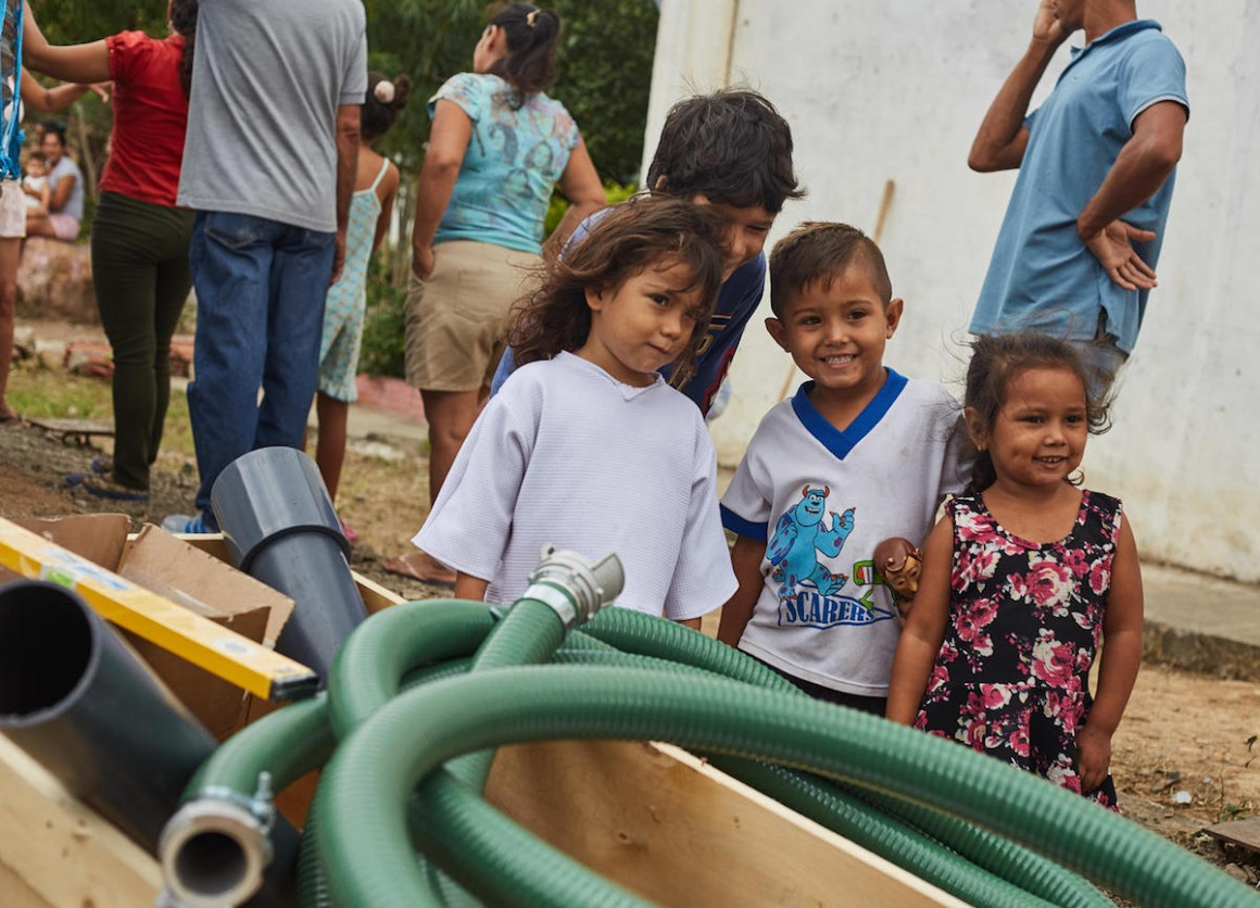 Children watch while UNICEF staff and partners install a water tank which will provide access to safe drinking water to an estimated 24,000 people a month in San Antonio, Tachira state, Venezuela.